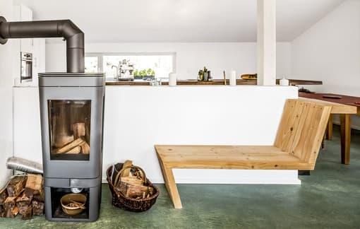 Im Innern schlagen viele Elemente aus Holz – unter anderem eine Kaminliege und die Treppe – den Bogen zum Holz.
