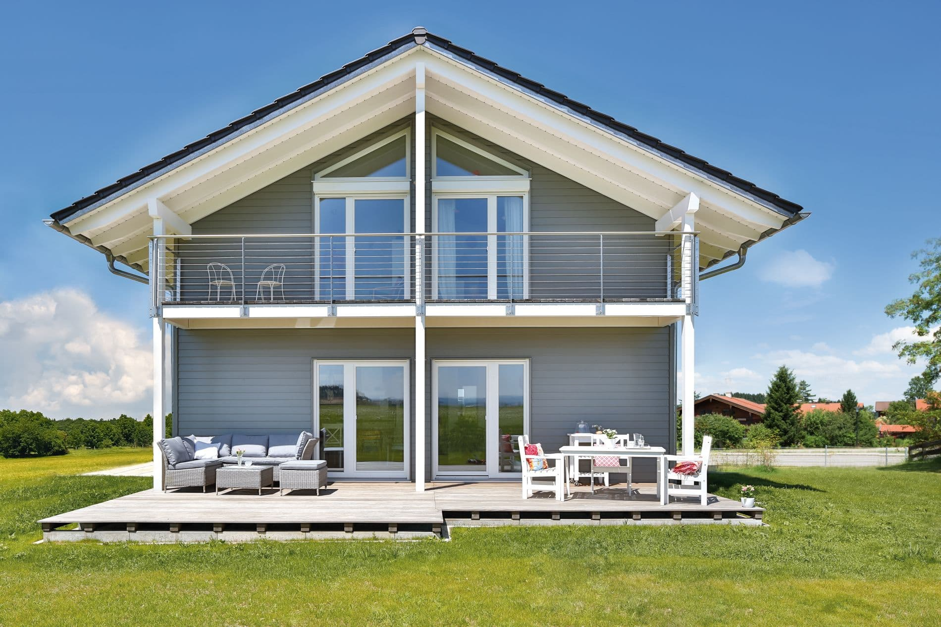 Dunkle Tonziegel, eine graue Schalung aus Holz, weiße Fenster. Dazu ein mit 26 Grad sanft geneigtes Satteldach, das als weit ausladendes Vordach ausläuft und an der Unterseite weiß angestrichen ist.