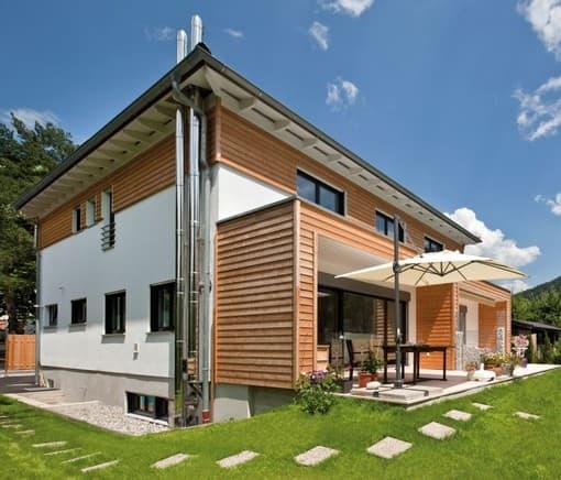 Zum Garten öffnet sich das Haus mit einem Freisitz, der sich über die ganze Frontseite zieht, in die Landschaft. Die Holz-schalung nimmt die Terrassenüberdachung wieder auf, sodass Haus und Veranda zu verschmelzen scheinen.