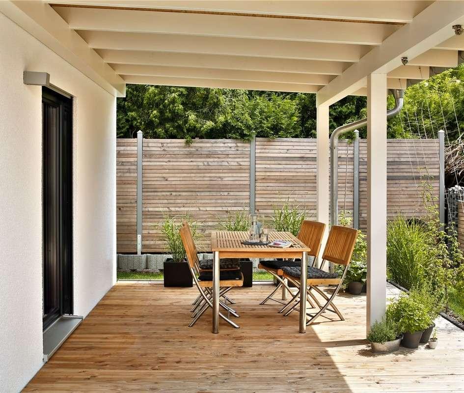 Im Süden und Westen öffnet sich das Haus und lädt zum Verweilen auf der umlaufenden Holzterrasse ein.