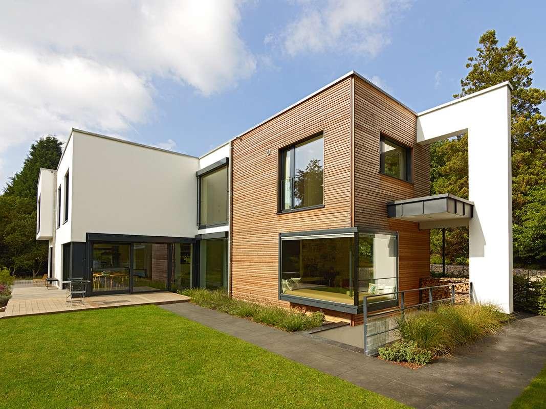 Durch die Mischung von weißer, biologischer Mineralputzfassade und einer naturbelassenen Holzverschalung schmiegt sich das Haus perfekt in die Umgebung ein. Die Familie gelangt über einen Privatweg, vorbei an großen Bäumen, zu ihrem Traumhaus, das eine perfekte Kulisse bildet.
