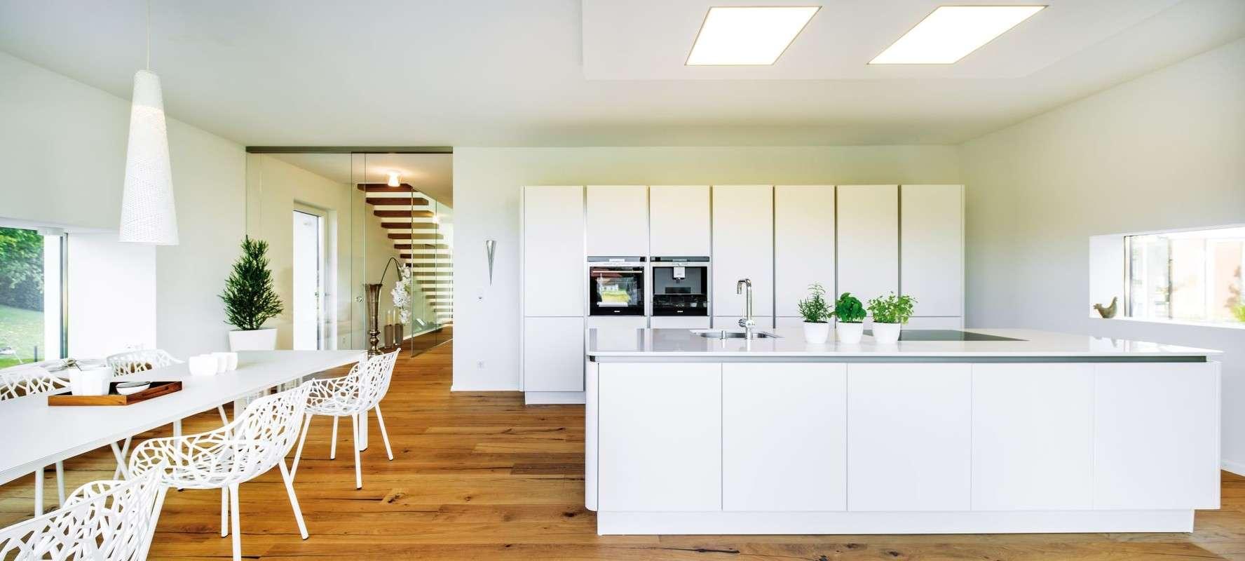 Das oft turbulente Leben einer Familie spielt sich im Erdgeschoss, dem zentralen Treffpunkt des Hauses, ab. Hier befinden sich der offene Koch- und Essbereich, ein WC, ein Gästezimmer und ein Büro.
