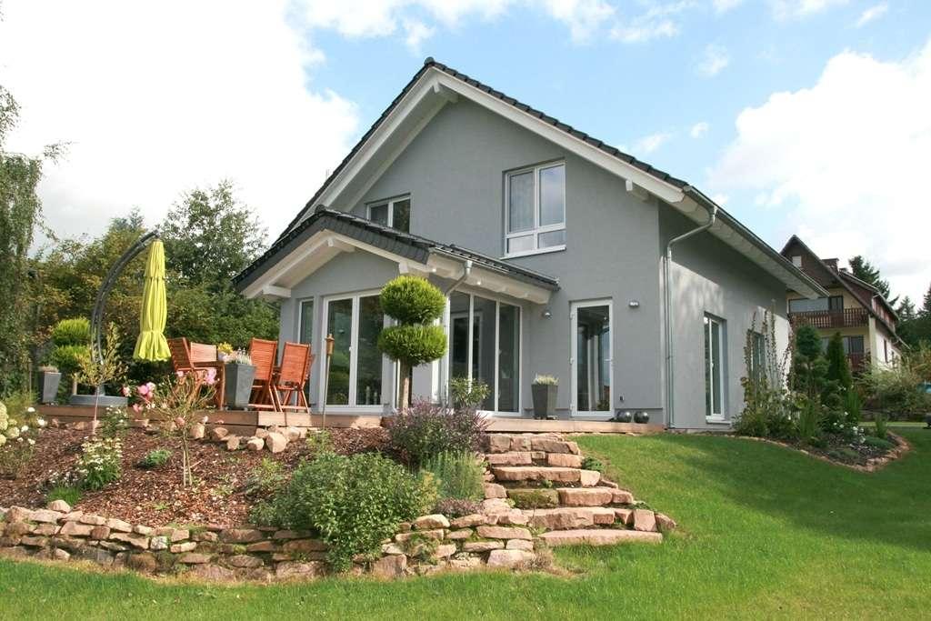 Moderne graue Fassade und kleiner Anbau zur Terrasse