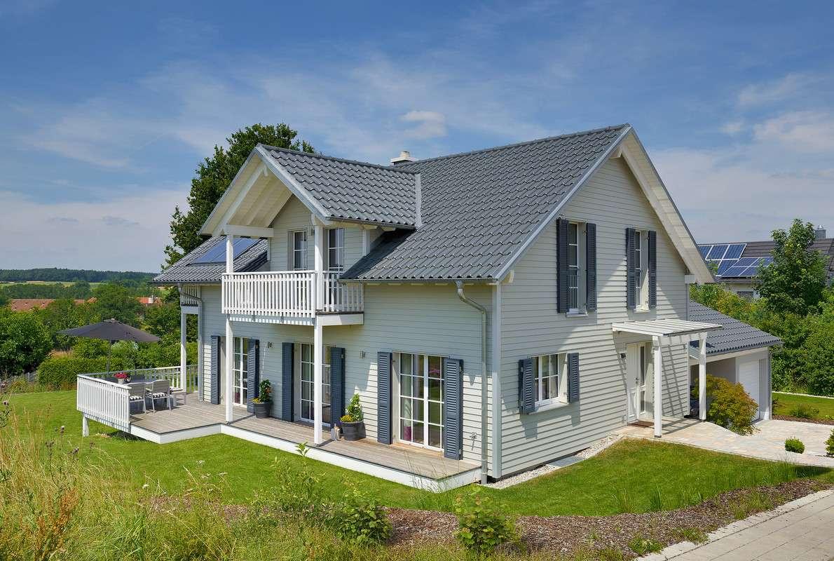 Das 148 m² große Einfamilienhaus mit dem Satteldach und der großen Veranda wurde in Oberbayern realisiert. Typisch für den Landhausstil ist der herausstehende Hausgiebel und die liebevoll inszenierten Details wie die Sprossenfenster, die Terrassentüren mit weiß gehaltenen Zierbändern und die weißen Geländer rund um die große Veranda und den luxuriösen Balkonplätzen.