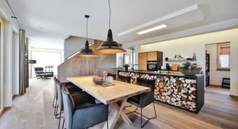 Im Koch-Wohn-Essbereich bietet ein 240 x 100 cm großer massiver Esstisch großzügig Platz für gesellige Tischrunden. Gekocht wird gleich daneben in der eigens angefertigten Schrei-nerküche mit den massiven, gezinkten Schüben aus Eiche Natur und dem modernen Backofen mit integrierter Mikrowelle und Dampfgarer.
