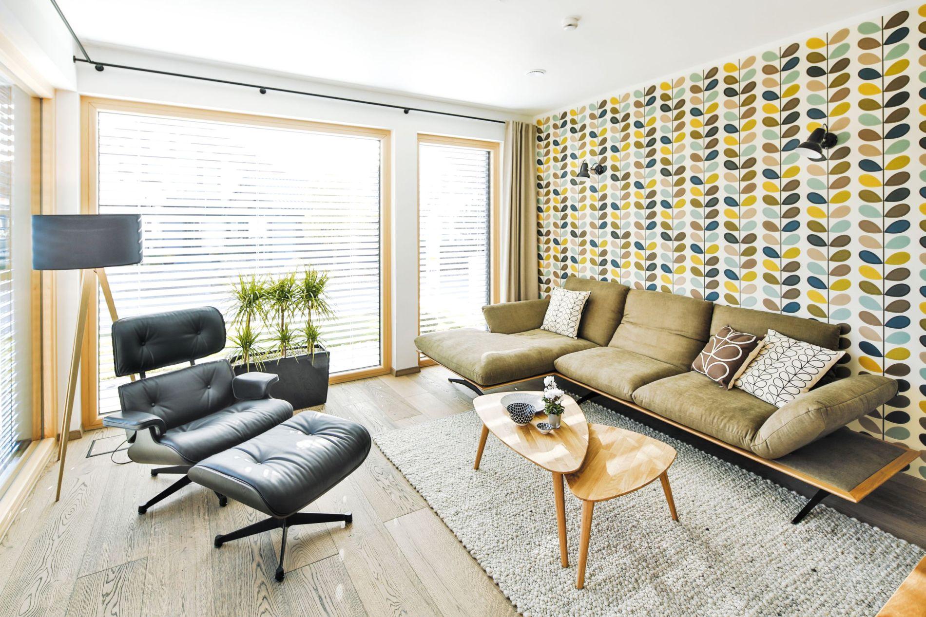 Im Wohnraum laden ein stylisches Sofa aus der neuen Dieter-Knoll-Kollektion sowie ein Eames Lounge Chair vor der modernen Retrotapete zu abendlichen Plausch-, Lese- oder Medienrunden ein.