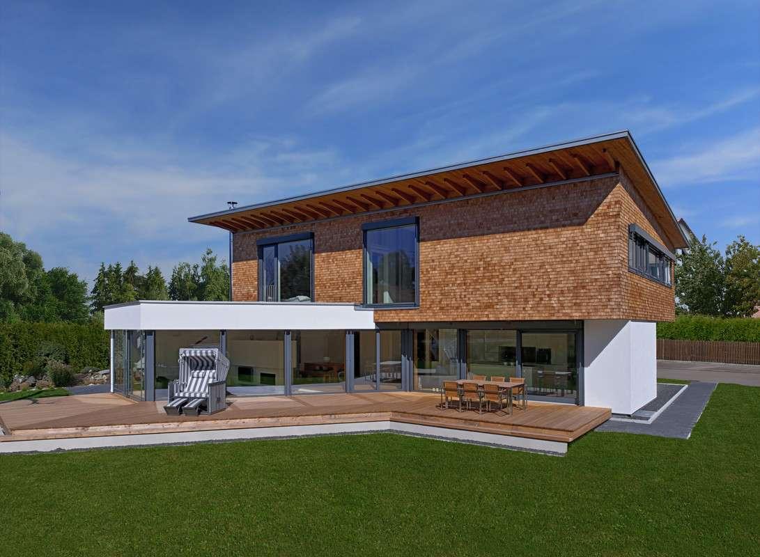 Dieses moderne Architektenhaus besticht nicht nur durch seine markante Architektur und die fast rustikale Schindelfassade. Es überzeugt gleichzeitig mit seinem weitläufigen Raumgefühl, welches durch großzügige Glasfronten unterstrichen wird.